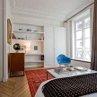 A red kilim rug, blue Eames chair and cool black globe add color to the all-white master bedroom.