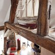 A model ship perched between wooden structural beams, with a birds-nest view of the living area.