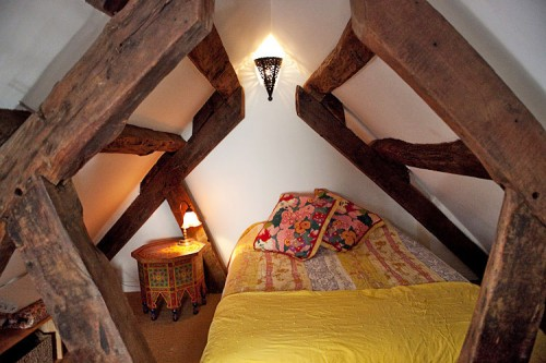 Framed by 350-year-old wooden beams, the tiny upstairs bedroom pops with mix-and-match patterns.