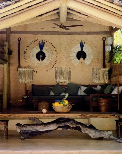 In the lounge area, dining table made from cashew tree trunk, recycled truck covers as pillows, and walls made of clay in traditional native style.