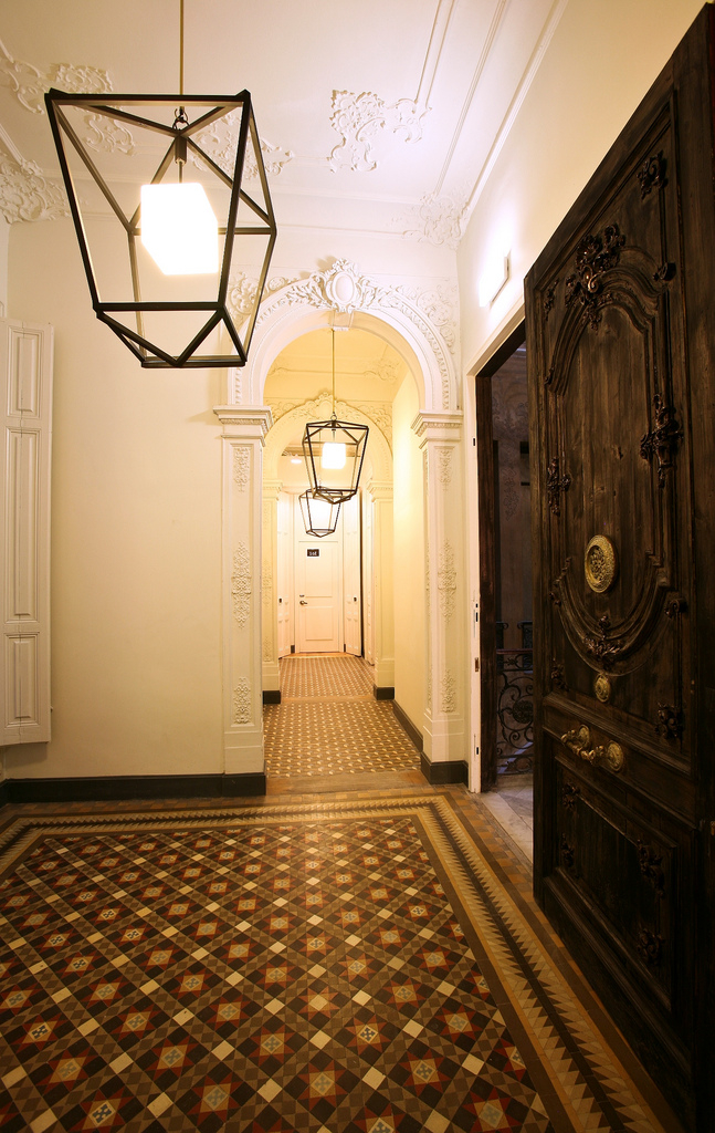 colorful floor tiles and oversized iron light fixtures in the hallway