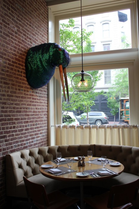 A huge glittering walrus head hanging over a cushy window booth in the restaurant--I Am The Walrus by Cuban native Enrique Gomez de Molina. The skin is made from thousands of jewel beetle wings and the tusks are made from swordfish bills.