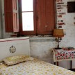 A sweet antique bed is tucked into a sprawling family room with a sitting area on the second floor. Granville elevates mixing and matching textiles to an art form.