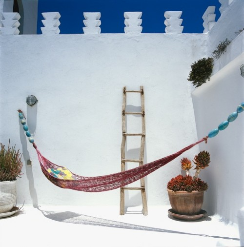 A colorful hammock is strung up in a nicely decorated corner of one of the outdoor areas.