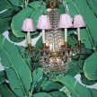 Dainty pink chandeliers paired with lush, leafy wallpaper by Carleton Varney--and it totally works.