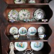 A curio in the living room filled with colorful dinnerware.