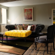 You can certainly see Joanna's edgy hand in this living room, where pops of yellow and raw wooden floors mix with tufted seating.