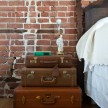 I stacked these vintage suitcases — one from my personal collection, the others from thrift shops around Detroit — to make a nightstand. And I trash-picked the headboard on bulk pick-up day.