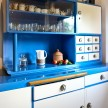 The blue kitchen cabinets were a gift from their neighbors, who also help with the garden.