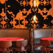 Flocked wallpaper and leather booths in the restaurant.