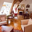 In the living area, parquet floors, a fireplace and a country dining table.