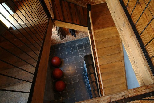 An open wooden stairwell leading to guest rooms.