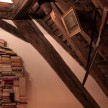 A haphazard floor-to-almost-ceiling pile of books gives this nook some literary-decor cred.