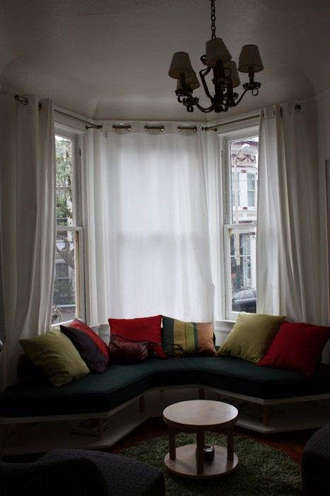 The cozy window seat looks out onto the street. You can see Cafe Soleil, an adjacent French cafe.
