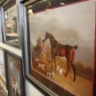 Endless horse paintings stretch down an enormous wall.