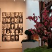 Trees made of old clothing (through all four seasons) in front of a collection of paintings of Cuban officials by Jose Toirac.