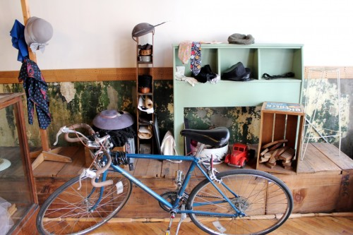 The incredibly lovely entryway with an antique counter (full of old brushes and tools), vintage hats and peeling plaster.