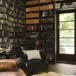 "The library/lounge with ""Genuine Fake Bookshelf"" wallpaper by Deborah Bowness."