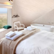 One of the bedrooms, which pools its soothing color palette from the sand and sea colors out the window.