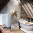 Soaking tub in the peaked-roof loo with exposed beams.