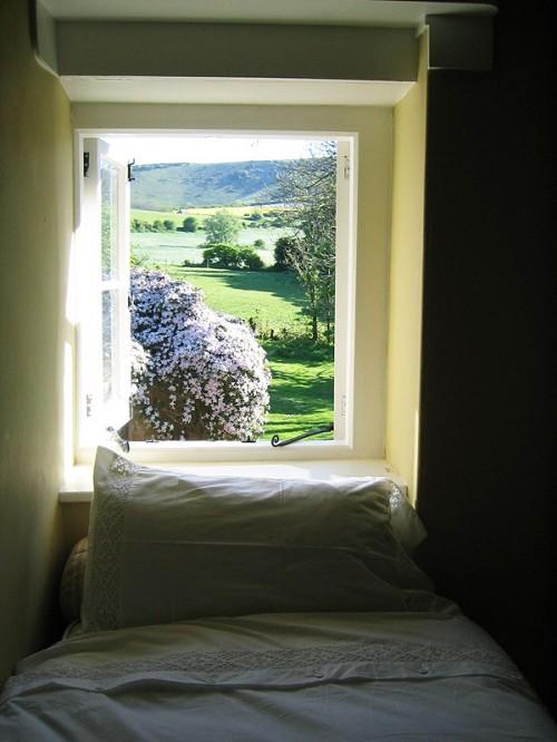 An open bedroom window flaunts the amazing views.