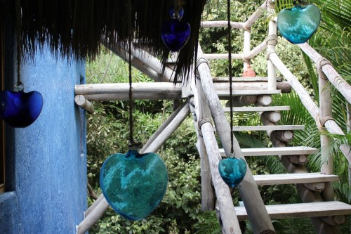 Glass-blown hearts hang by rope near the stairs.